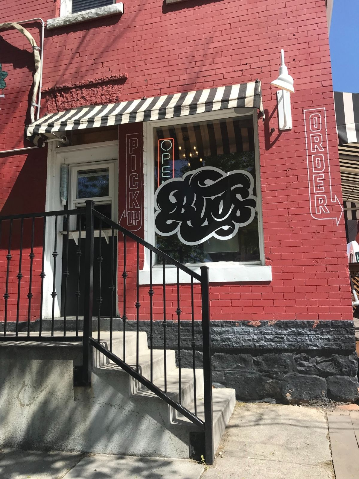 front of buds storefront, red brick, logo on window, steps leading to pickup window