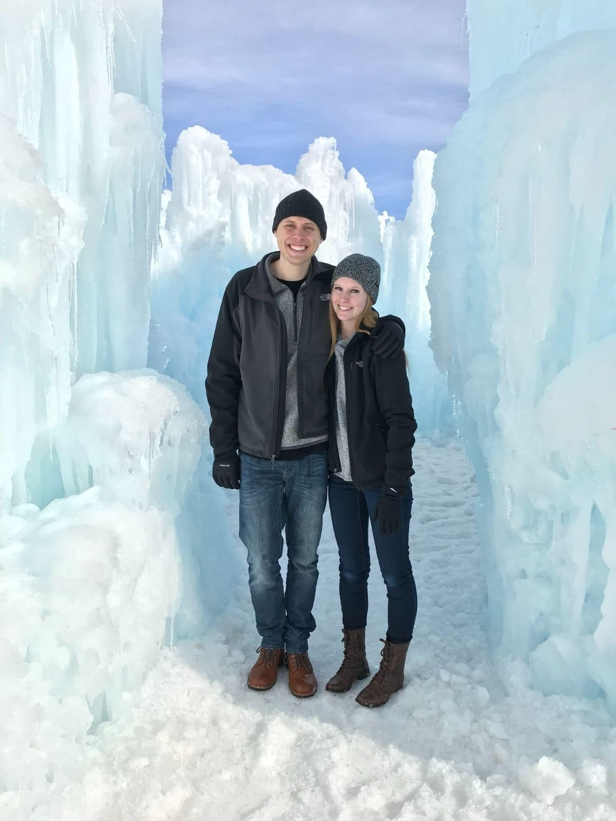 a couple standing in the snow at the ice castles in midway utah surrounded by ice sculptures