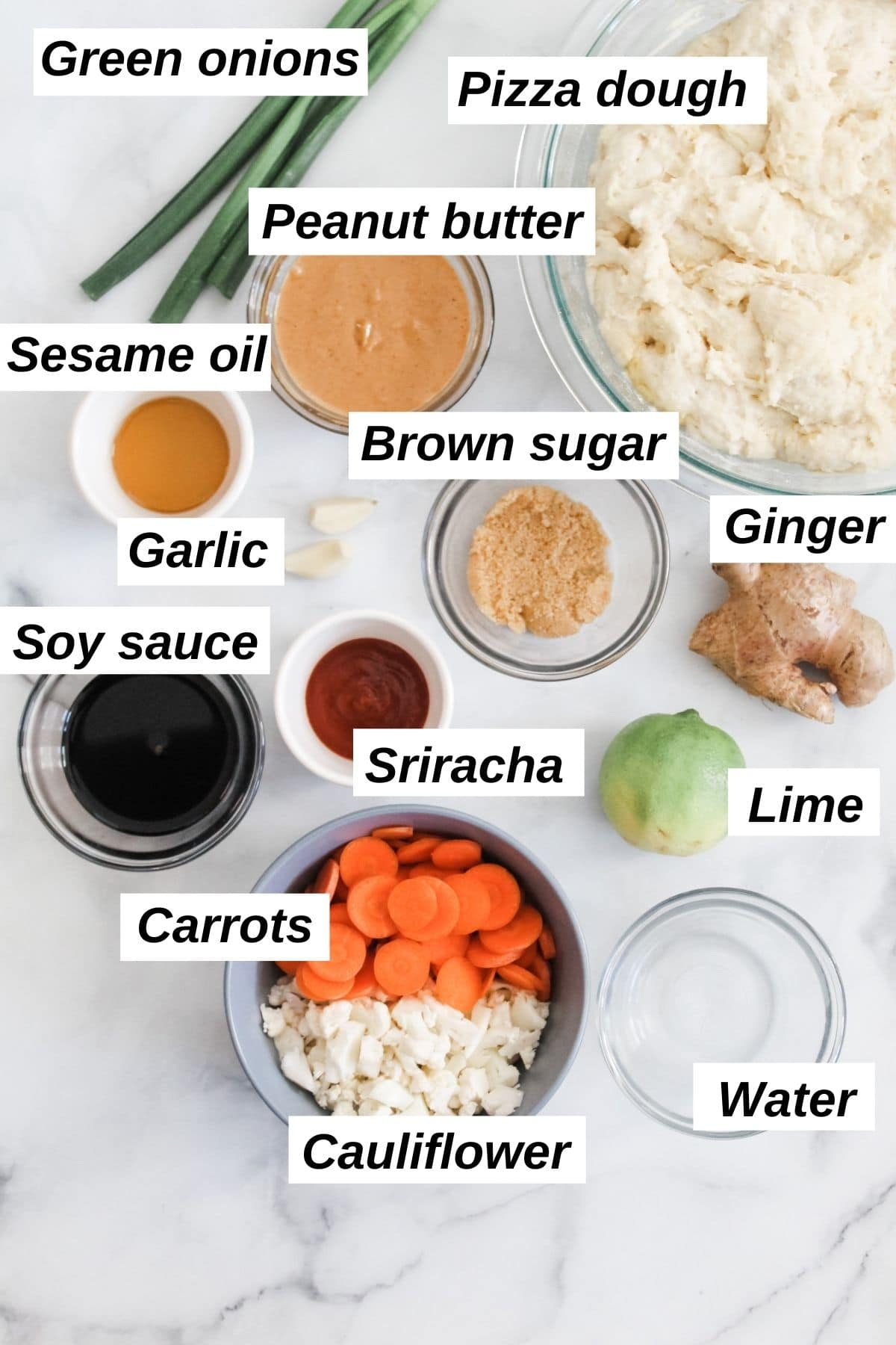 ingredients for vegan thai pizza in little bowls including peanut butter, cauliflower, sesame oil, carrots, ginger, and more