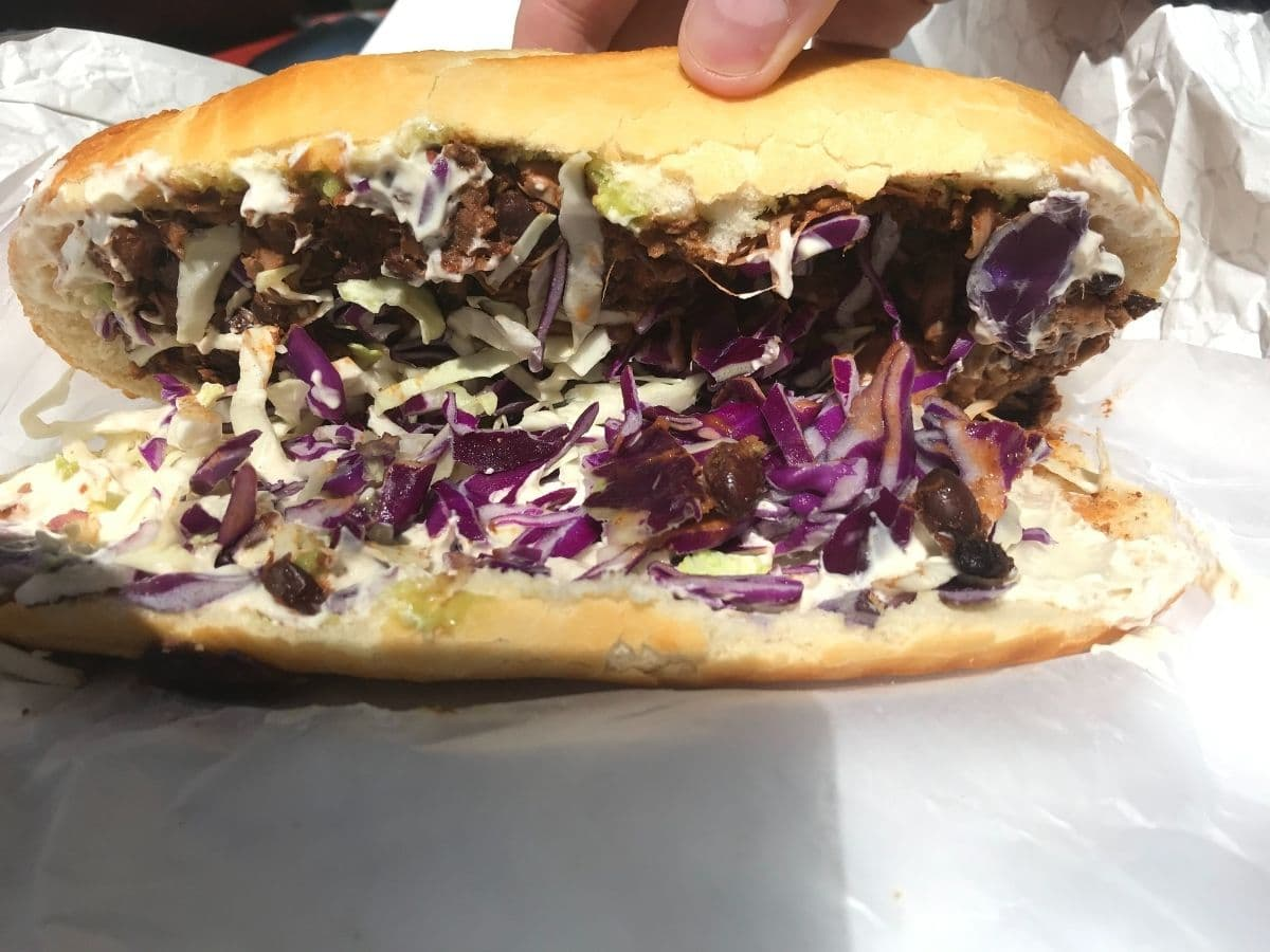 jackfruit barbacoa sandwich with sourdough bread opened up so you can see inside the sandwich, topped with purple cabbage