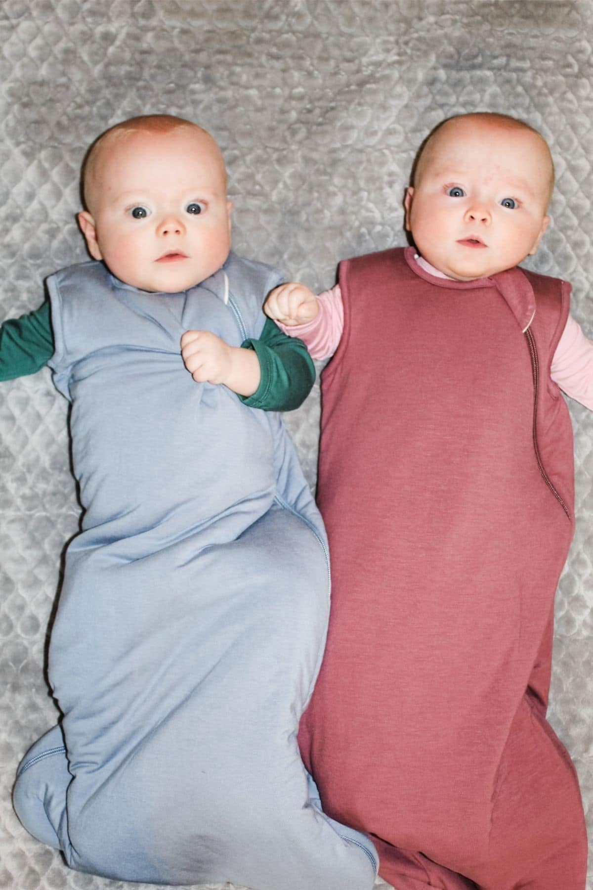 twin babies in kyte baby sleep bags that are blue and purple laying next to each other on a grey blanket