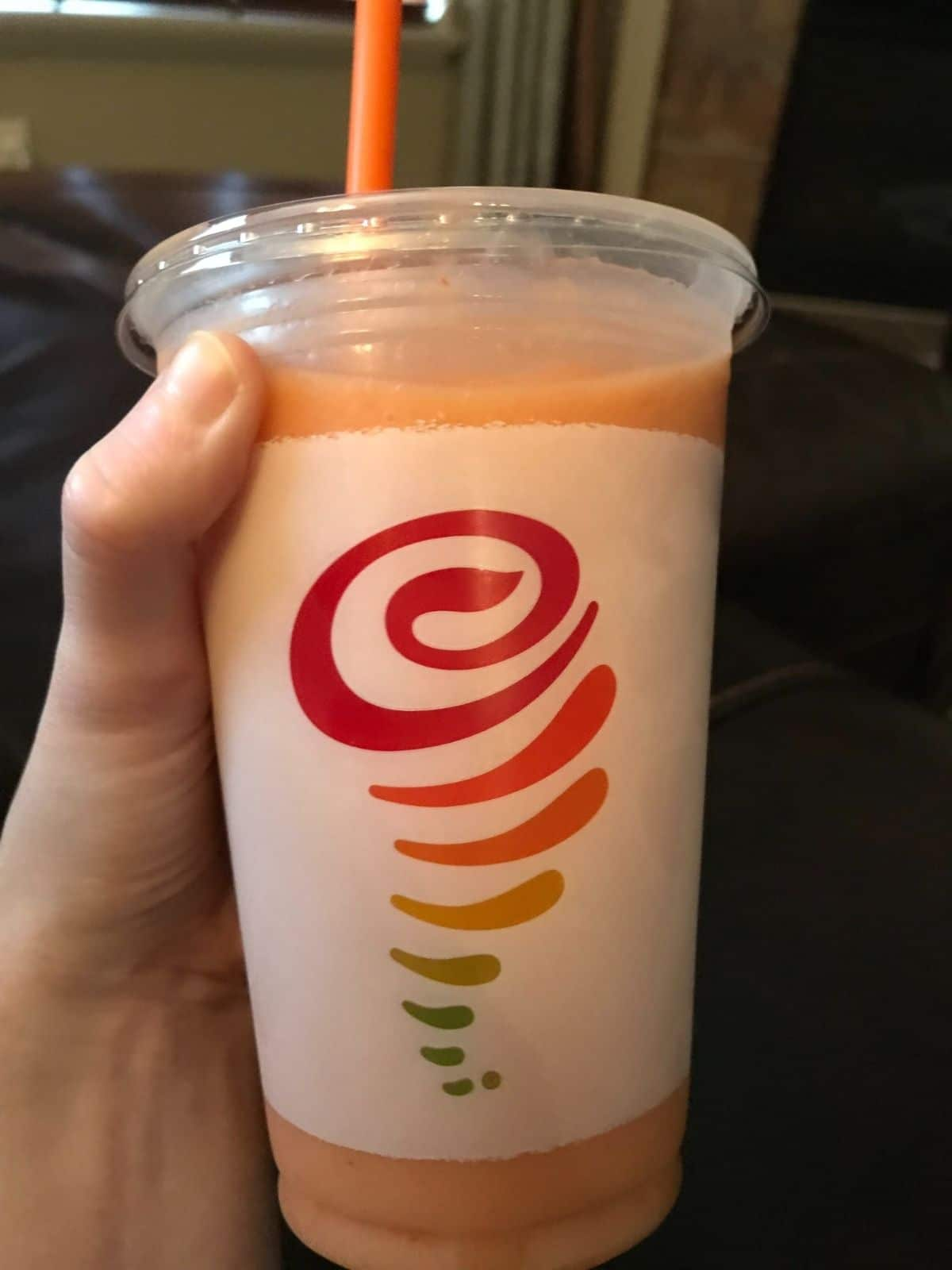 mega mango smoothie from jamba juice being held in a hand with a dark background