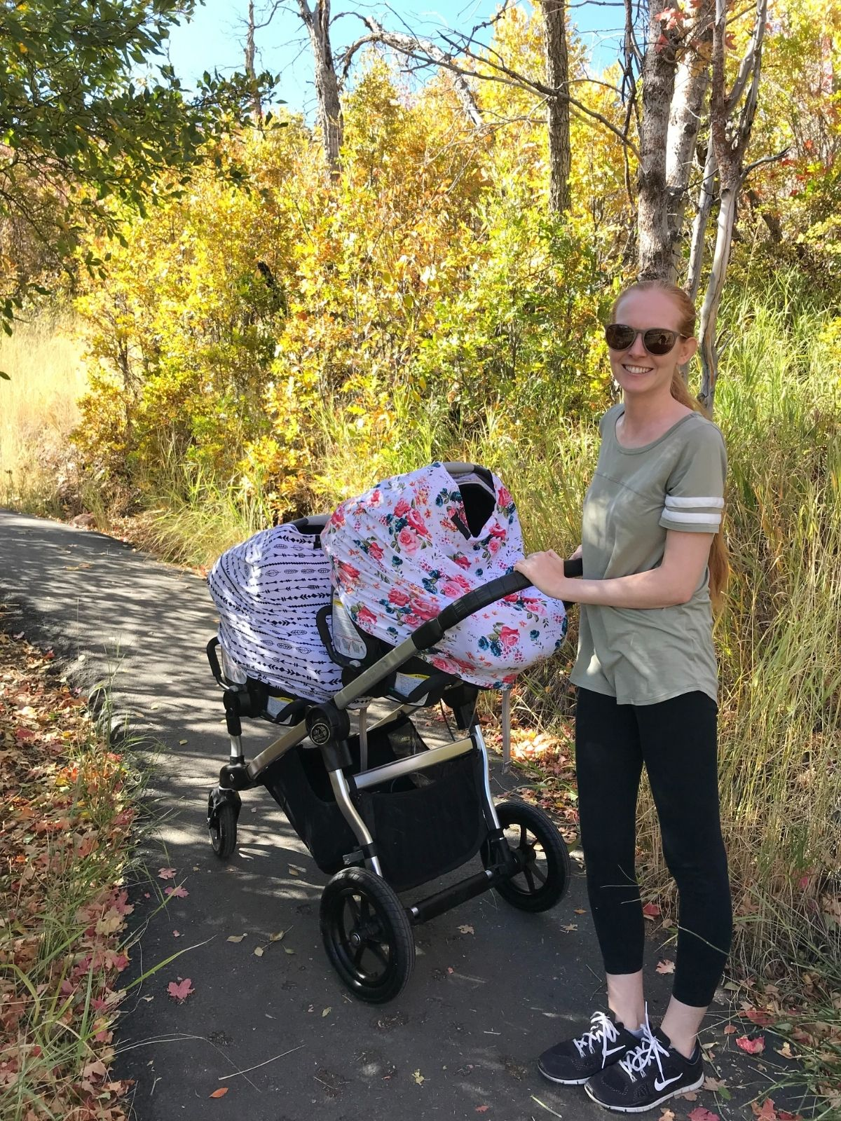mom pushing double stroller with twins in car seats with car seat covers on a path in the fall
