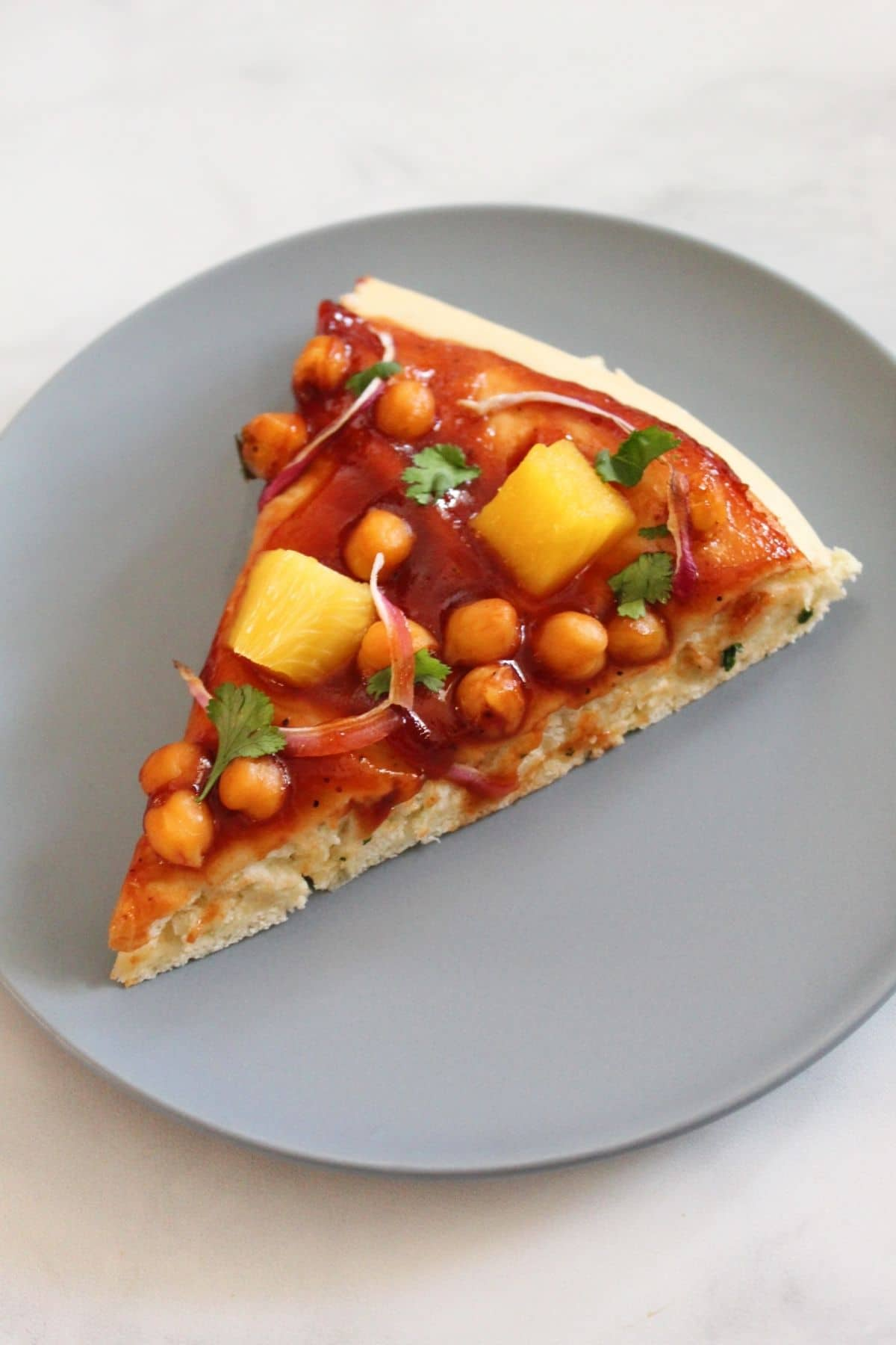 one slice of vegan barbecue pizza on blue plate