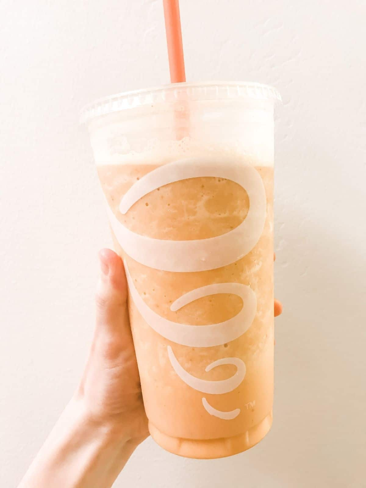 pumpkin smash plant based smoothie in a jamba juice cup with an orange straw, being held up against a light background