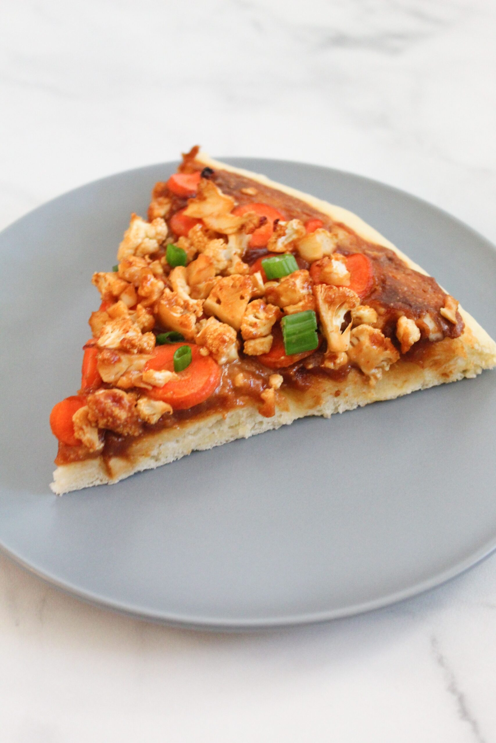 slice of finished thai pizza topped with green onions on blue plate