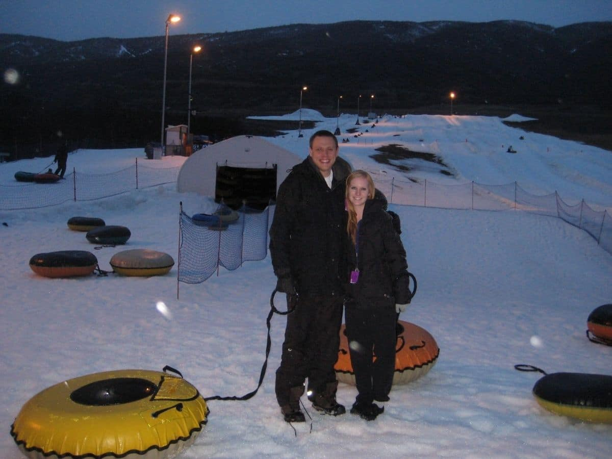 a couple standing in the snow at soldier hollow snow tubing at night