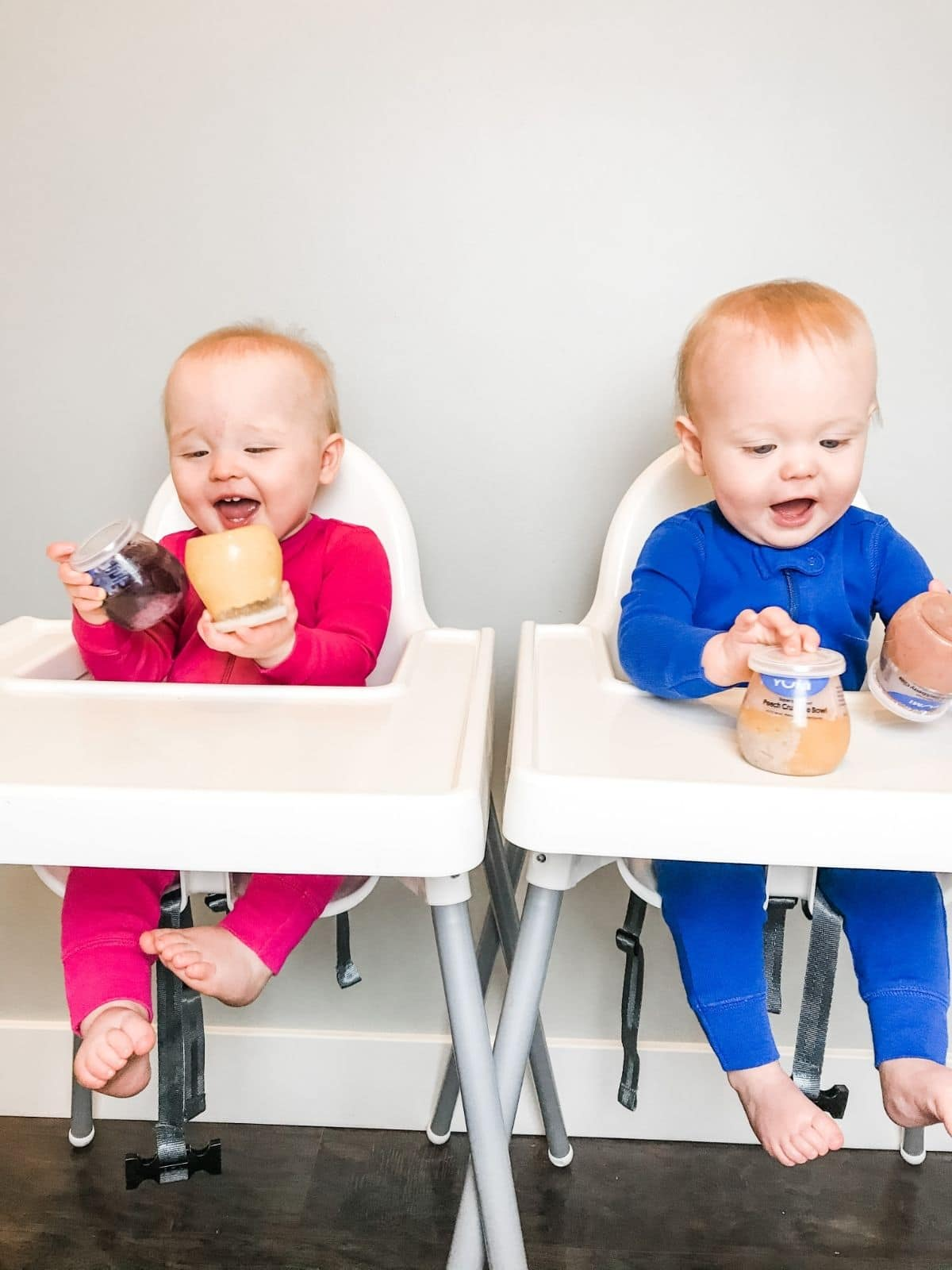 twin babies wearing pink and blue in high chairs playing with baby food jars
