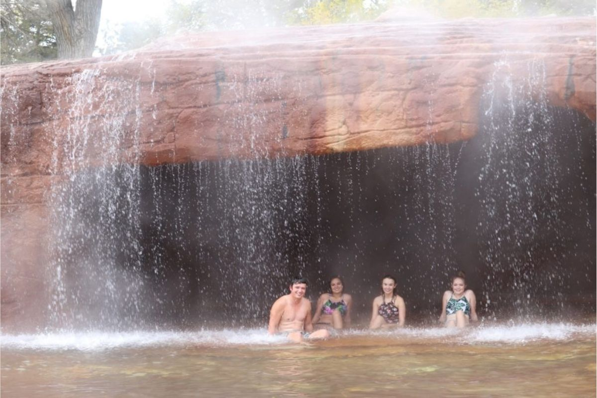 1 guy and 3 girls sitting underneath waterfall at crystal hot springs in honeyville utah