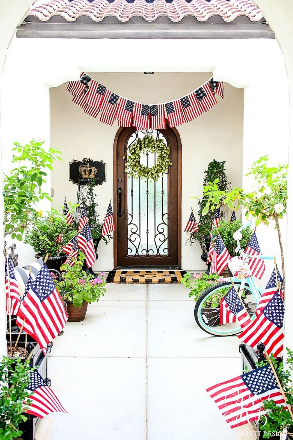 4th of July porch with a path of american flags and a flag banner over the door
