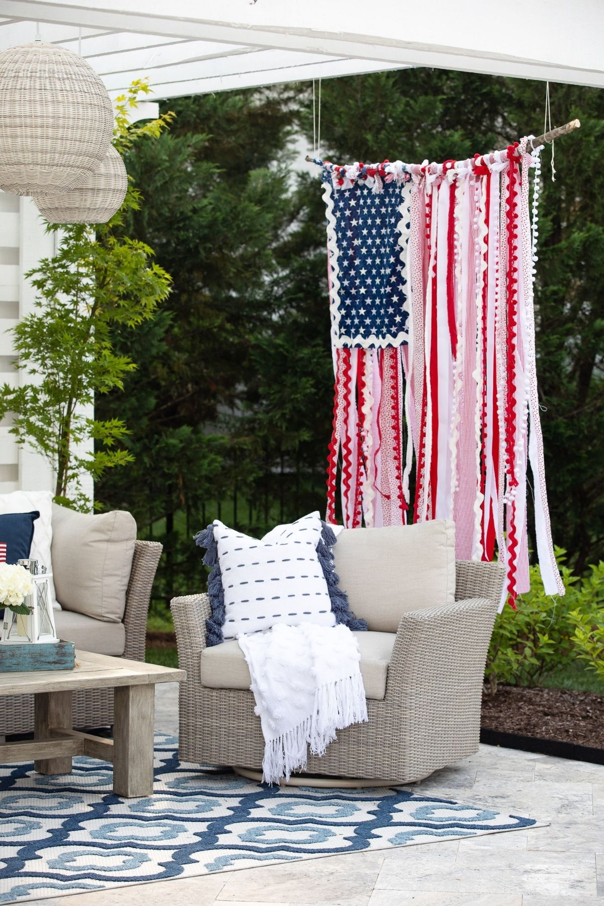 hanging american flag made with rags next to porch furniture