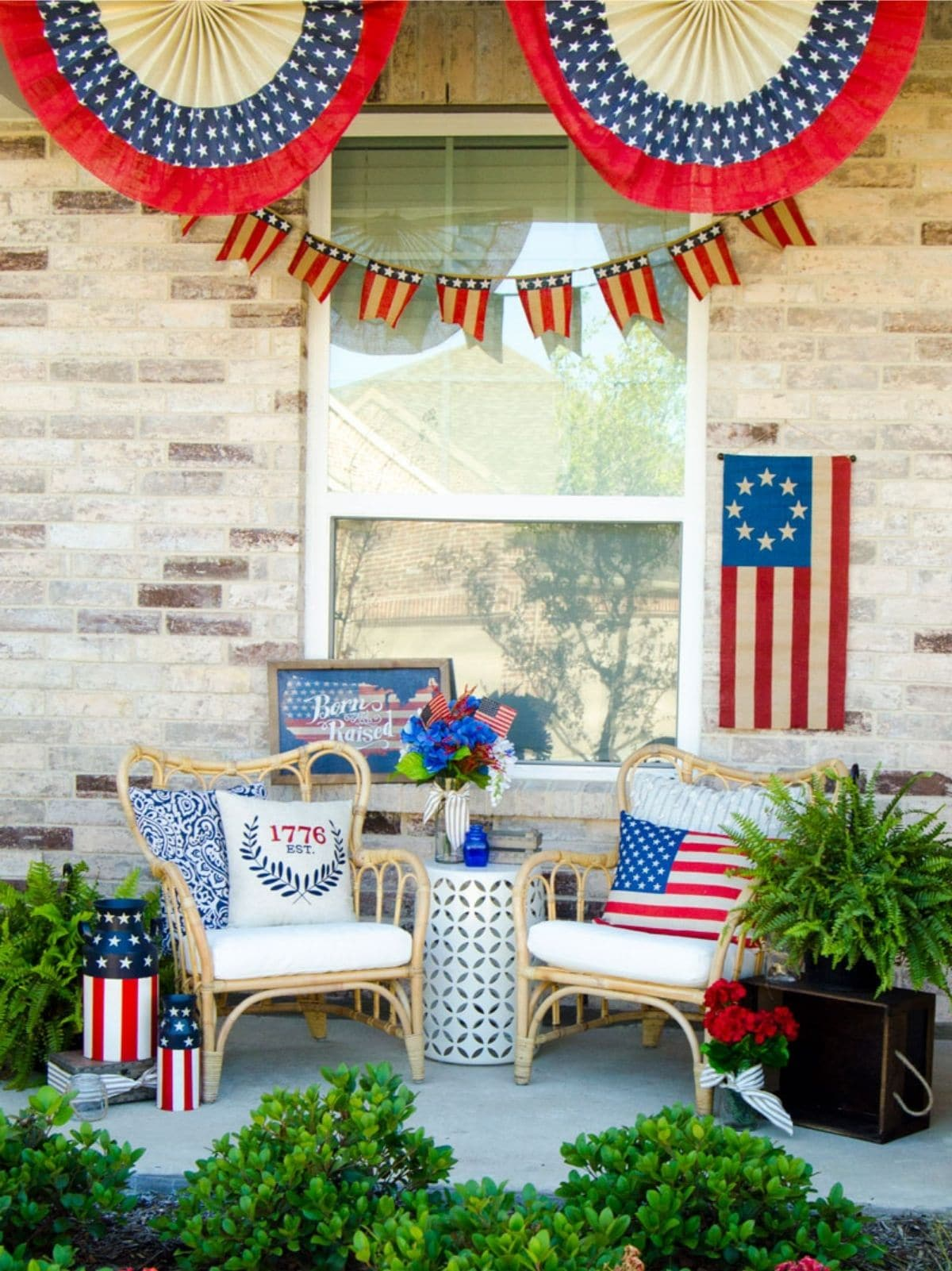 porch with wicker chairs, patriotic throw pillows and flags