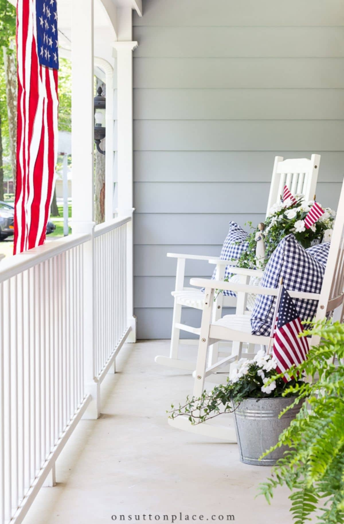 porch with white rocking chairs, decorative pillows, and hanging american flag
