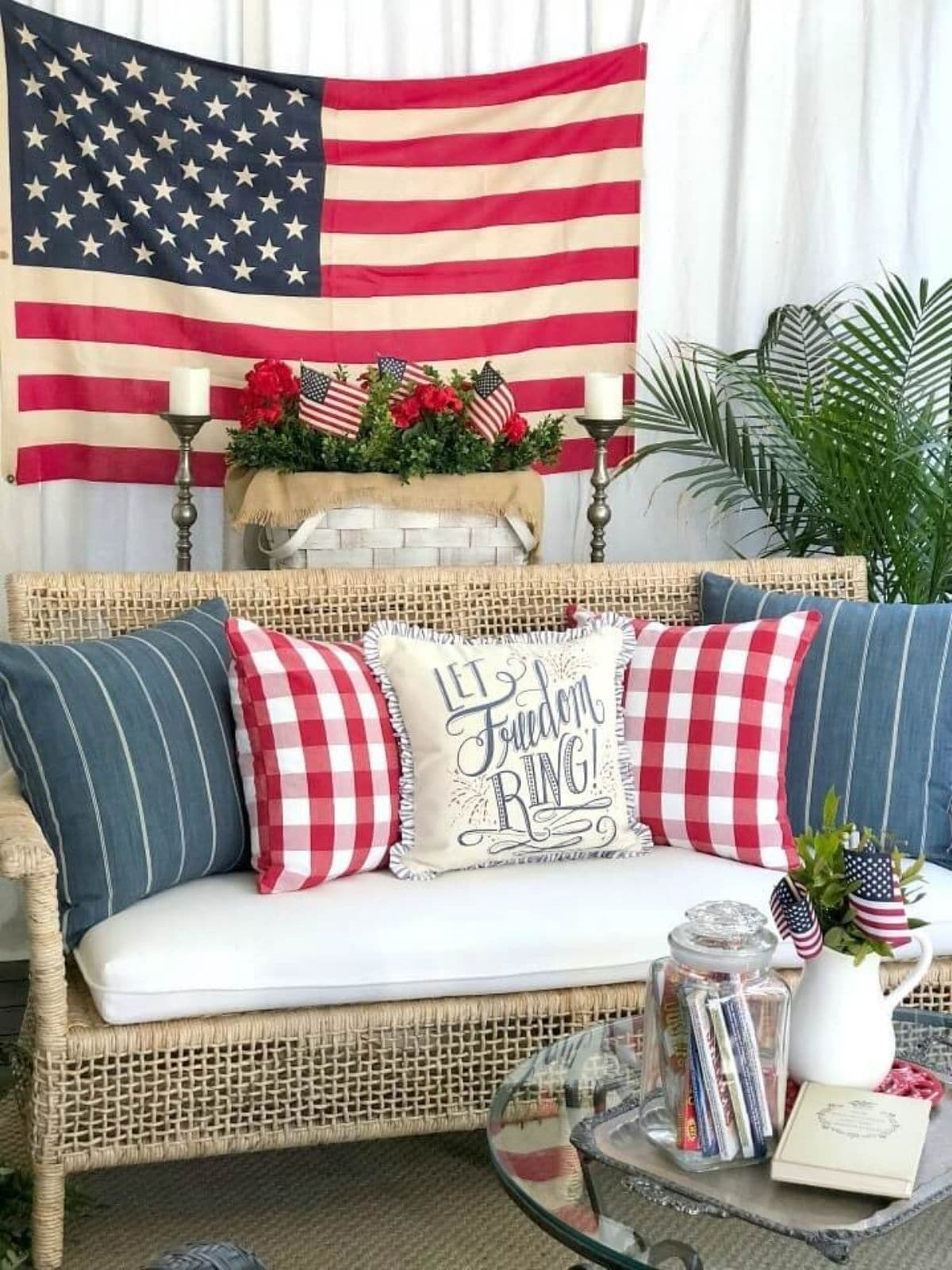 porch with wicker bench with 4th of july pillows and american flag in the background