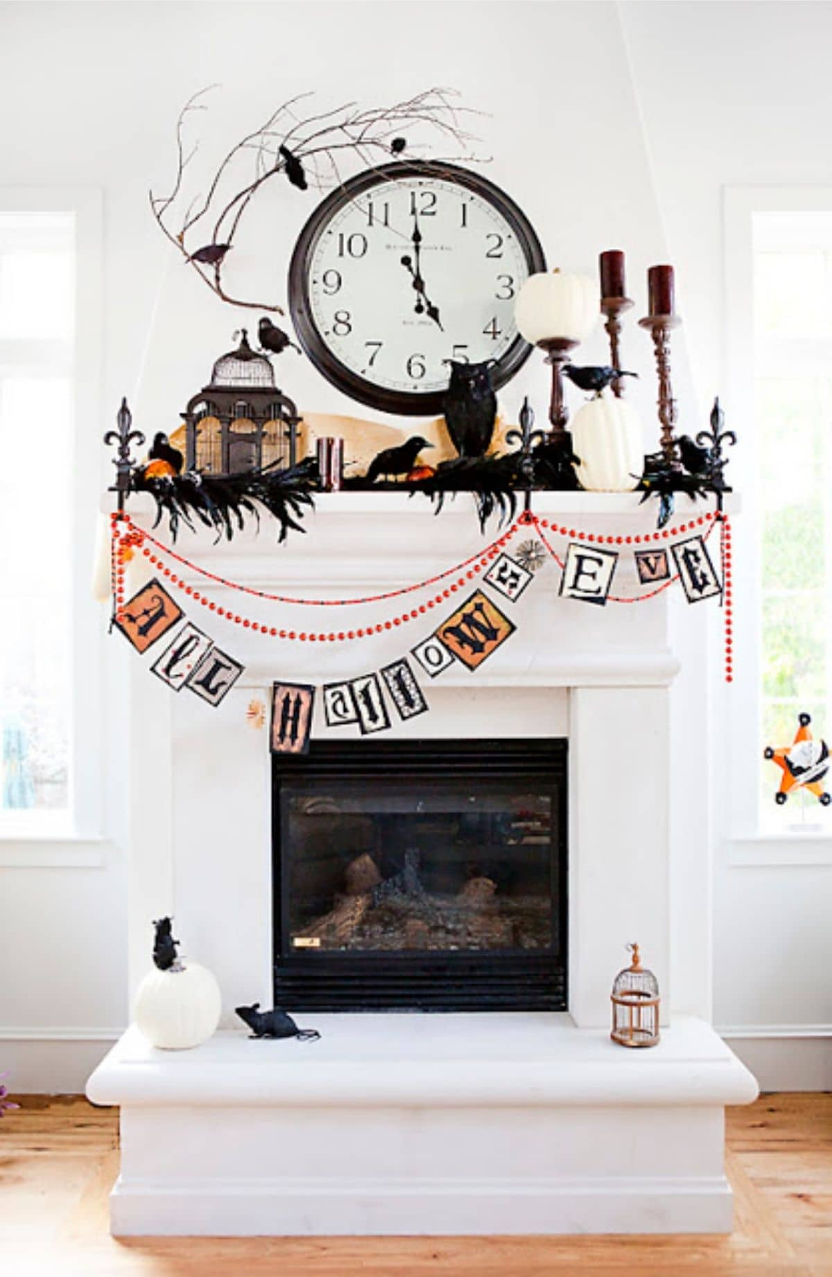 mantel that says all hallow's eve and decorated with black birds and owl