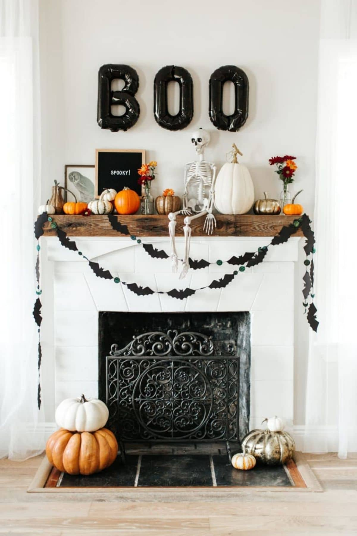mantel decorated with a skeleton and balloons that spell BOO