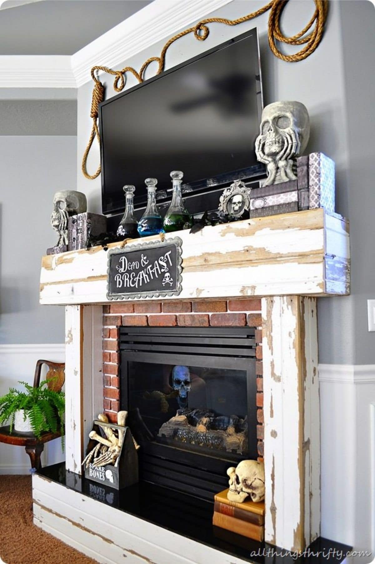 halloween mantel decorated with skulls, potions, and picture that says Dead & Breakfast