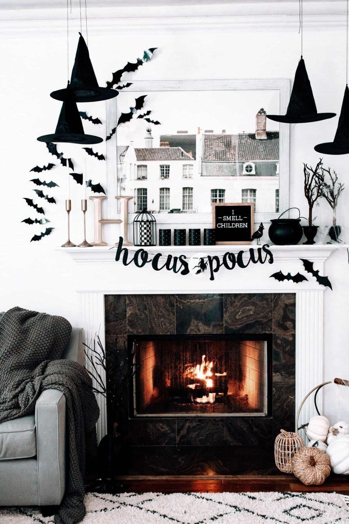 mantel with a banner that spells Hocus Pocus, hanging hats, and bats