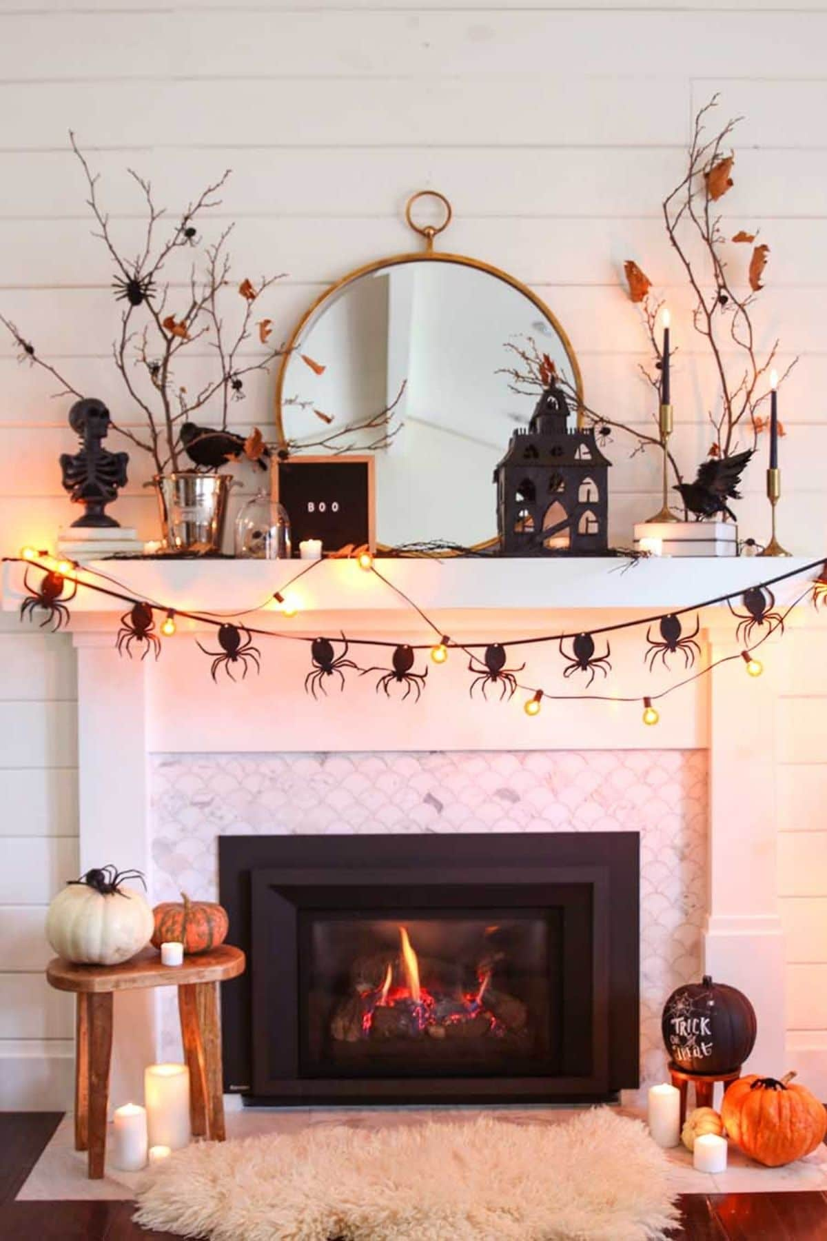 halloween mantel with spiders, pumpkins, and branches