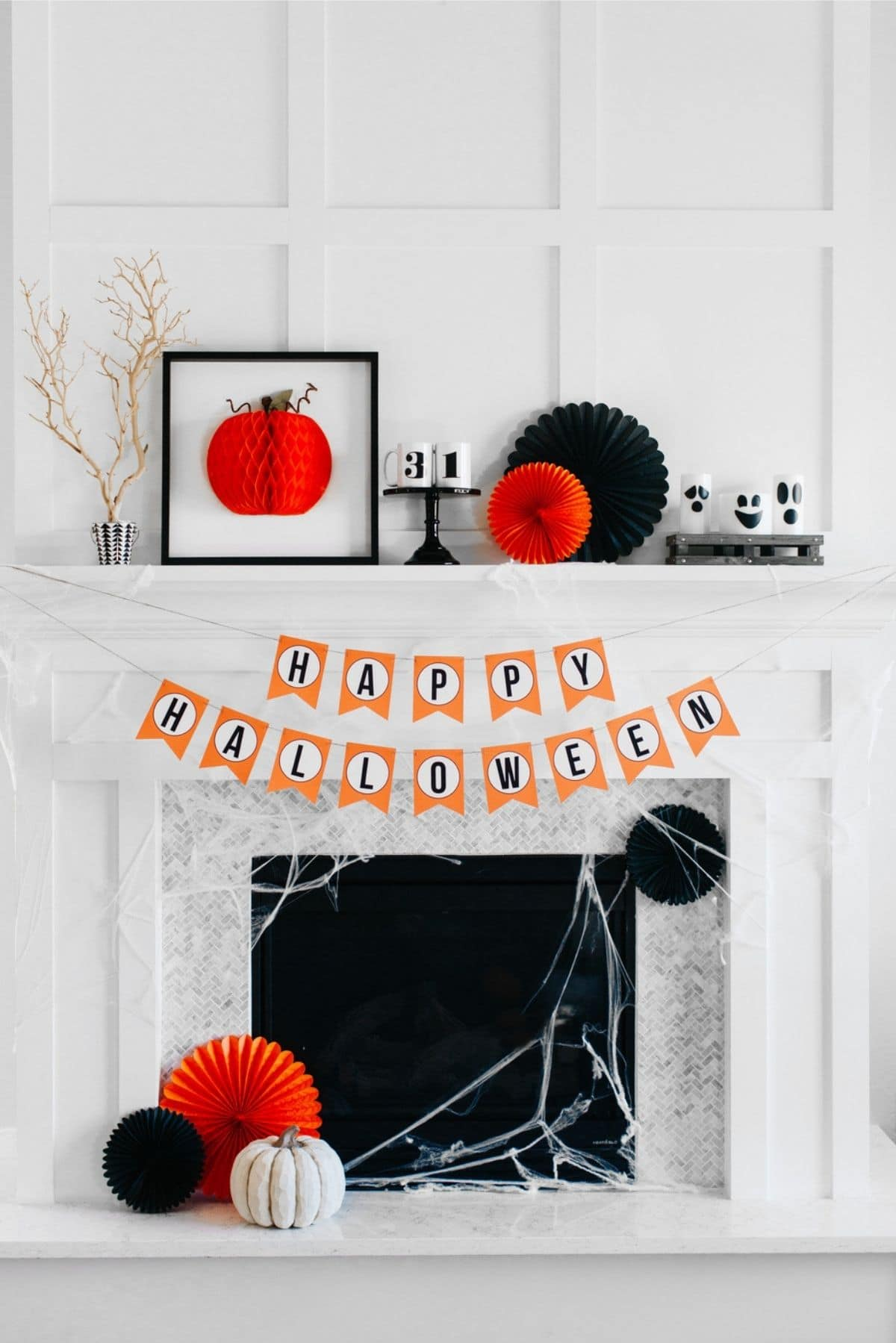 mantel with a happy halloween banner and ghosts