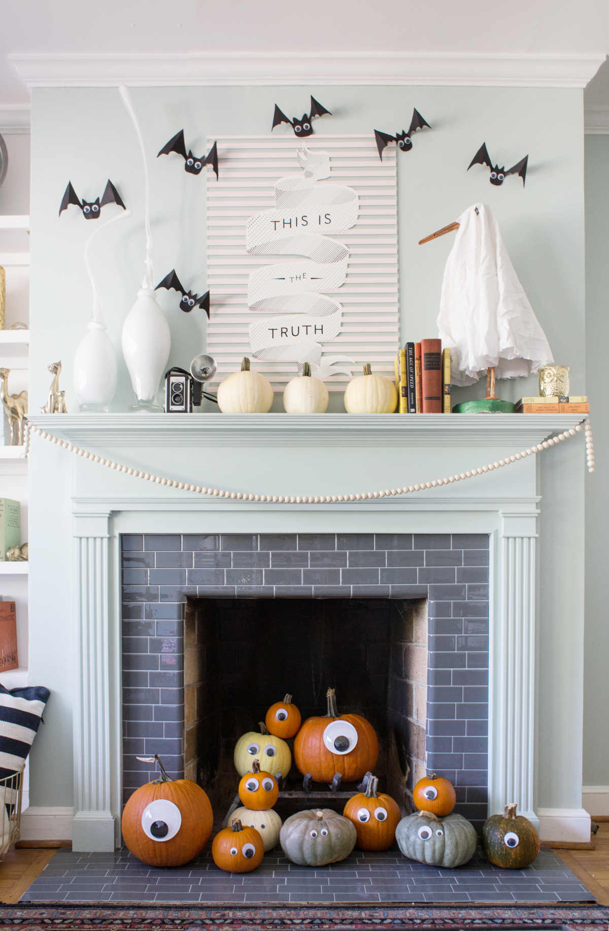 mantel with bats, ghost, and white pumpins