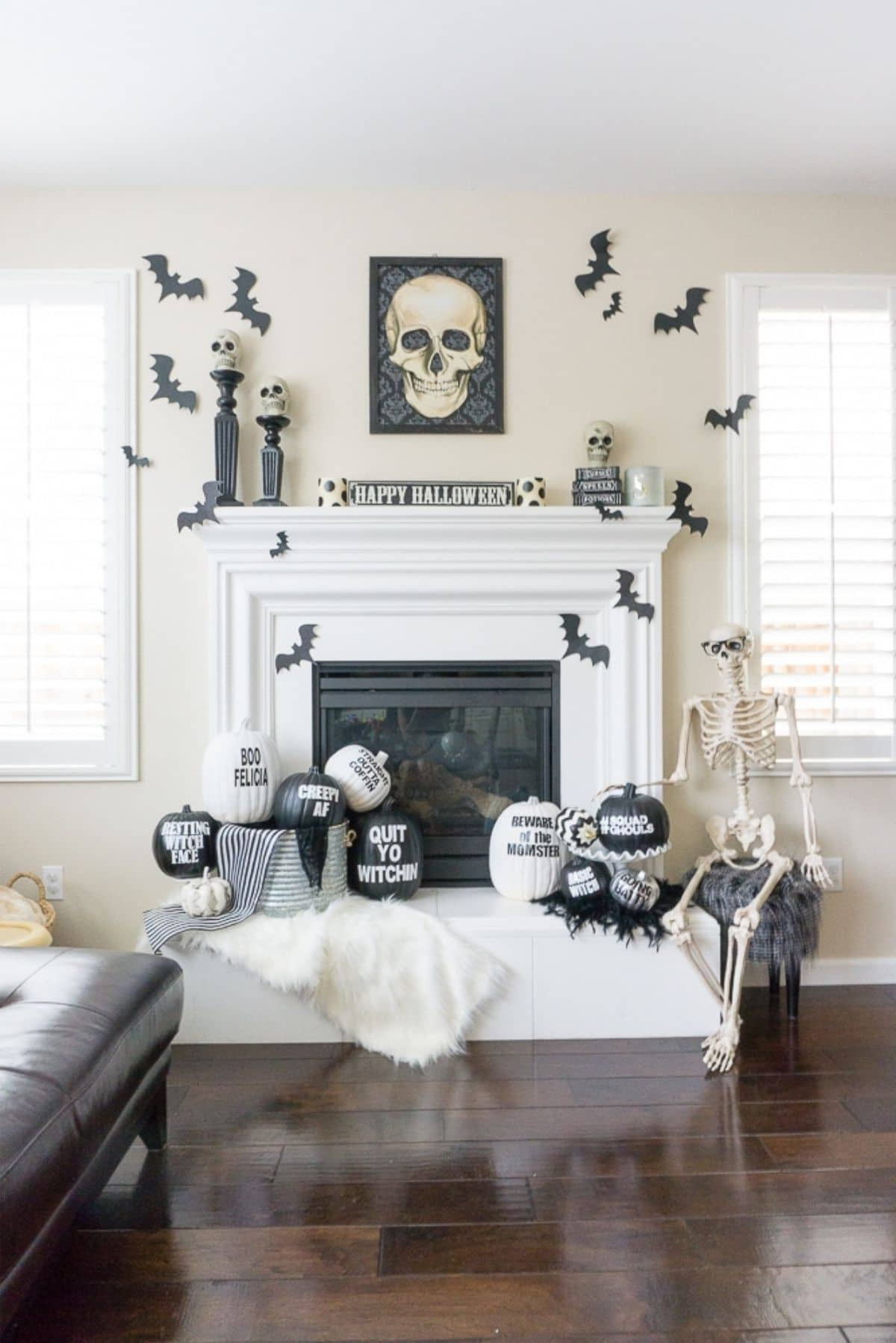 mantel with skulls, bats, pumpkins with sayings on them, and a big skeleton