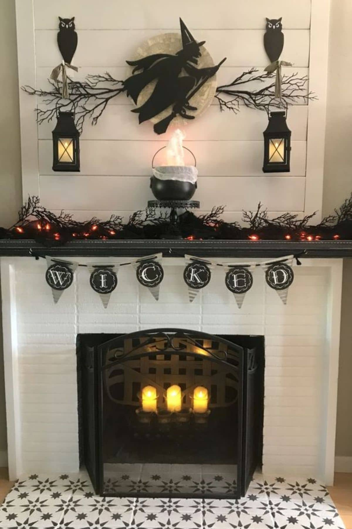 mantel with black owls, lanterns, cauldron, and banner that says Wicked