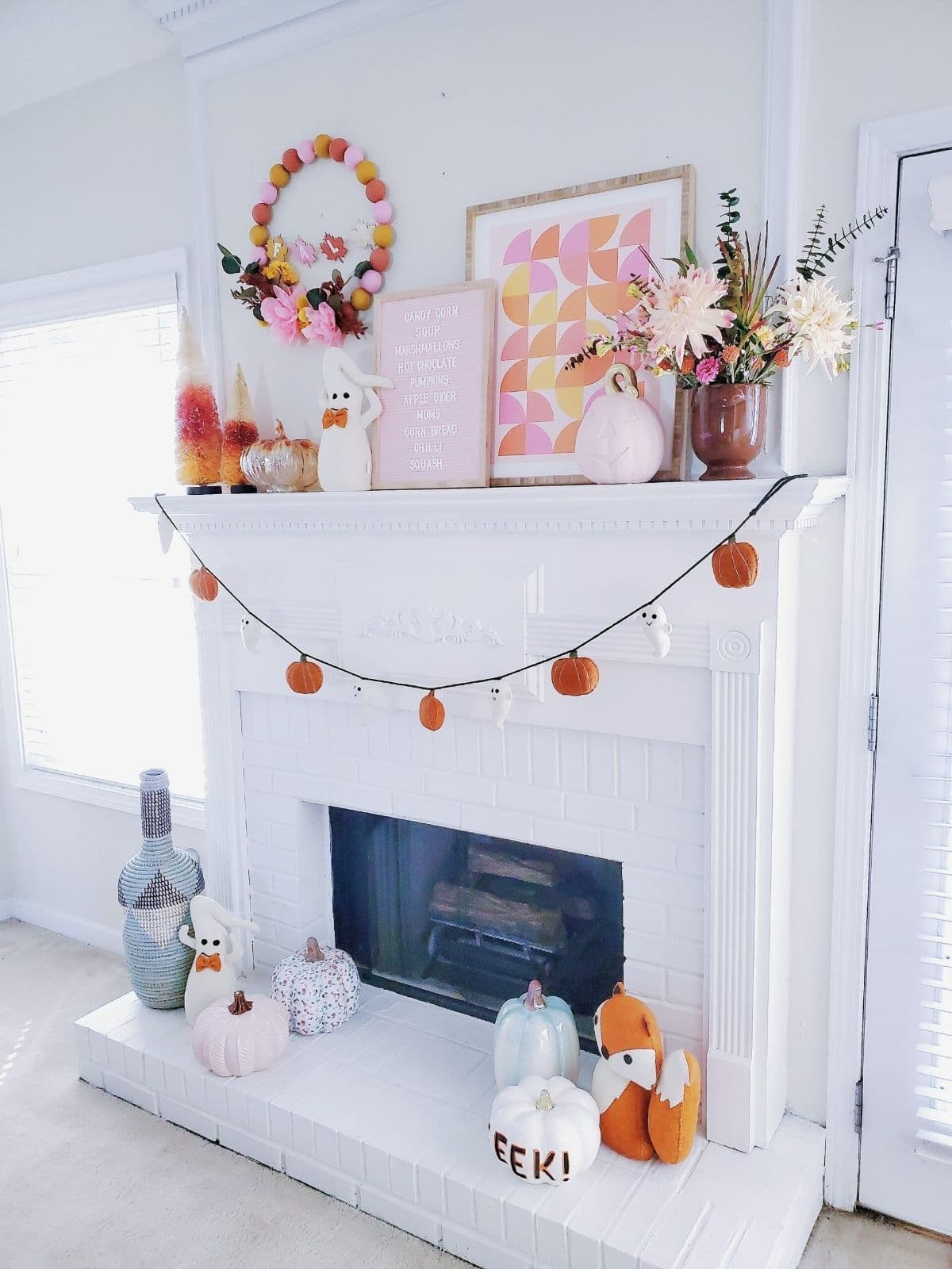 halloween mantel with pink pumpkins and ghost banner
